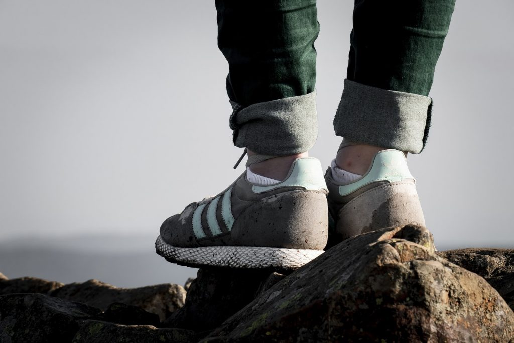 Feet standing on rocks visible ankle